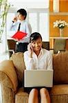 Femme sur le canapé, avec ordinateur portable et téléphone mobile, l'homme en arrière-plan