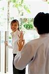 Woman holding door open, waving at man