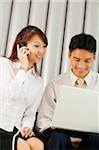 Femme sur téléphone mobile, l'homme à ses côtés à l'aide d'ordinateur portable