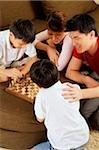 Famille avec deux enfants jouant aux échecs