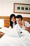 Couple dans la chambre, en regardant pour ordinateur portable, l'homme à l'aide de téléphone portable