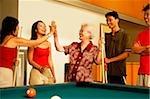 Three generation family around pool table