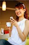 Jeune femme tenant de la coupe et téléphone mobile, souriant