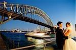Braut und Bräutigam stehen, Wegsehen, Brücke und Fluss im Hintergrund