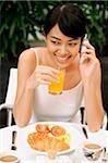 Femme prenant son petit déjeuner, à l'aide de téléphone portable