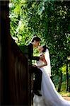 Bräutigam sitzt auf der Mauer, die Braut küssen
