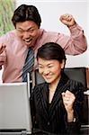 Gens d'affaires avec des expressions excitées, regardant le moniteur d'ordinateur