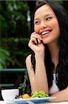 Femme assise à table de café, à l'aide de téléphone portable