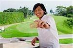 Homme tenant la carte de crédit, souriant à la caméra, parcours de golf derrière lui