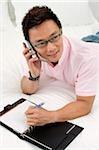 Homme couché sur le lit, à l'aide de téléphone portable, ordinateur portable ouvert devant lui