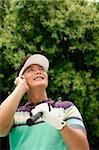 Male golfeur avec GSM, levant, souriant