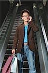 Homme sur l'escalator, porter les sacs, à l'aide de téléphone portable