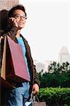 Homme avec les sacs à provisions, à l'aide de téléphone portable