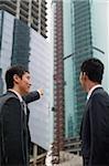 Hommes d'affaires dans la ville, regardant les bâtiments en arrière-plan