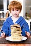 Kleiner Junge einen Stapel von Pfannkuchen essen