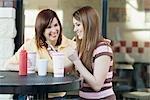 Mutter und Tochter trinken Pop und Pommes frites auf der Terrasse des Restaurants Essen
