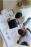 Two men crouching looking over blueprints, using laptop set on floor