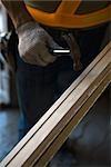 Worker holding hammer against wood