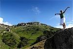 Femme levant ses bras dans les montagnes du Drakensberg, Kwazulu Natal, Afrique du Sud