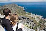 Vue grand angle du jeune couple regardant vers le bas en mer du point de vue sur montagne, Cape Town, Province du Western Cape, Afrique du Sud