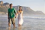 Jeune couple se promener dans les vagues avec la montagne de la Table dans le fond, Cape Town, Western Cape Province, Afrique du Sud