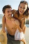 Homme donnant à son partenaire un piggy back sur la plage de Cape Town, Western Cape Province, l'Afrique du Sud