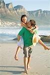 Homme donnant à ses partenaires une ride de greffer sur la plage avec la montagne de la Table dans le fond, Cape Town, Western Cape Province, Afrique du Sud