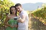 Jeune couple en prenant une photo de soi dans les vignes à Cape Town, Western Cape Province, Afrique du Sud