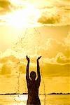 Une silhouette de femme éclaboussures de l'eau dans l'air au coucher du soleil, île Maurice