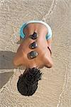 Femme de vue grand angle assise en eau peu profonde avec pierres de massage sur le dos, des aiguilles, Province occidentale du Cap, en Afrique du Sud