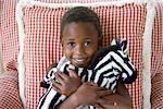 Young girl hugs a fluffy zebra toy, KwaZulu Natal Province, South Africa