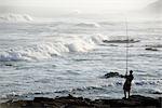 Silhouette d'un homme de pêche sur les rochers