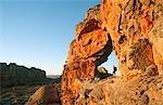 Randonneur debout dans une arche rocheuse naturelle