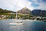 Un bateau à voile hors Clifton Beach avec la montagne de la Table derrière