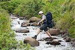 Hiker Boulder Hopping Across a River
