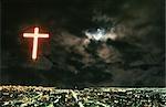 Lumières de la ville de Over de croix illuminée avec la lune qui brille à travers les nuages