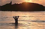 Silhouette d'une femme dans l'océan, à l'aube