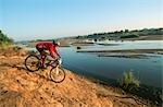 Mountain Biker Desending to the Riverbank
