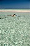 Homme de plongée en apnée dans les eaux claires d'un banc de sable de l'Atoll