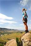 Femme debout sur les rochers à la recherche le paysage