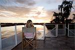 Femme en fauteuil Regarde un coucher de soleil sous les palmiers de pont du bateau-logement. Rivière Okavango, près de Shakawe, Botswana