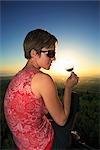 Fille de dégustation de vin comme le soleil se couche dans les vignobles du Cap au-dessus de Stellenbosch, Western Cape Province, Afrique du Sud