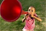 A little girl blows a vuvuzela. Johannesburg, Gauteng Province, South Africa
