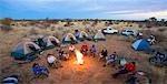 Bikers sit around a fire at camp, Central Kalahari Desert, Botswana