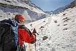 Femme randonnée jusqu'à un flanc de montagne couvert de neige