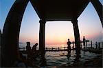 Gens assis dans les bains chauds au coucher du soleil