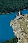 Homme assis sur une falaise surplombant un lac Turquoise et les forêts de pins