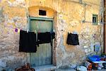 Vêtements sur une corde à linge à l'extérieur d'une maison ancienne avec peeling murs à Corleone sur l'île de la Sicile, Italie, Europe