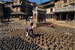 Mann mit Reihen von Tontöpfe Trocknen in Potters Square in Bhaktapur in der Nähe von Kathmandu, Nepal, Asien