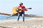 Kleiner Junge, die Gitarre zu spielen, am Strand